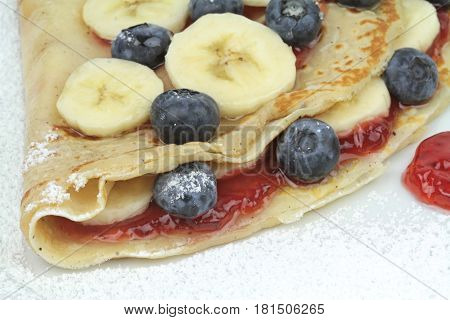 Crepe with strawberry jam, blueberry and banana slices close up image