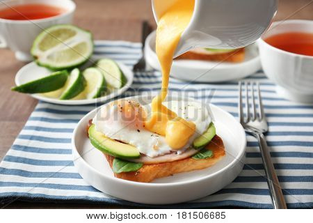 Pouring hollandaise sauce onto egg Benedict on plate