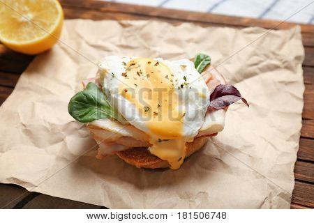 Tasty egg Benedict on wooden board, closeup