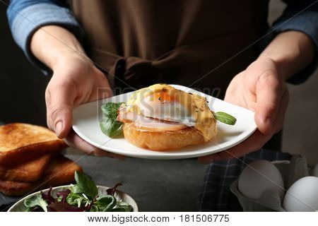 Female hands holding plate with tasty egg Benedict