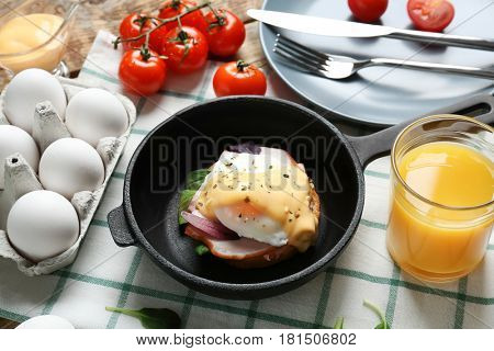 Frying pan with tasty egg Benedict on table