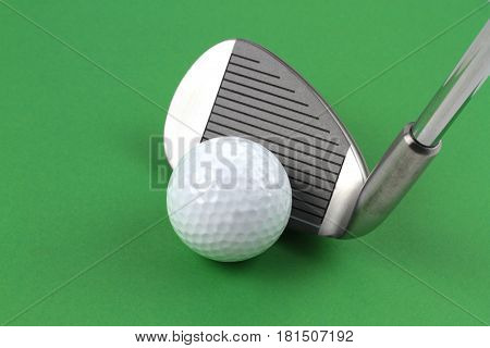 Golf club and ball on green background
