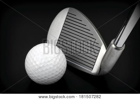 Golf club and ball on black background .