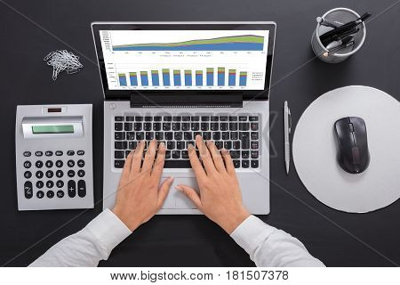 Close-up Of A Businesswoman Analyzing The Graph On Laptop At Workplace