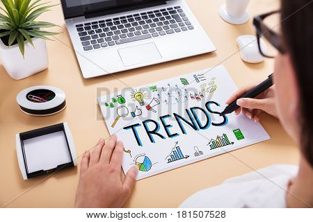 Close-up Of A Businessperson Drawing Trends Chart On Office Desk At Workplace