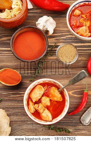 Portions of chicken tikka masala with different spices on wooden table