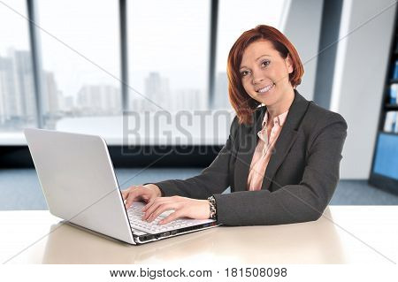 Happy business woman with red hair smiling at work typing on computer laptop at modern office desk sitting in front of the window at business financial district