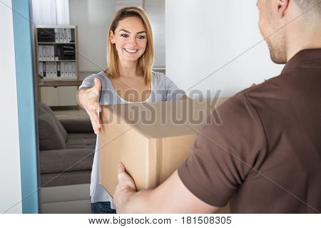 Excited Woman Looking At Cardboard Box Hold By Delivery Man