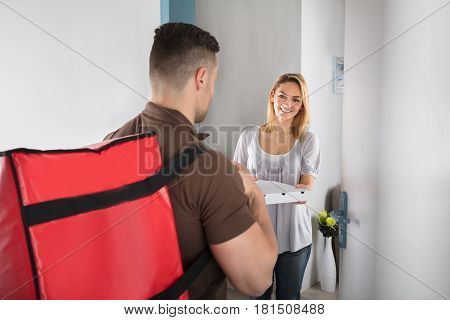Happy Woman Looking At Pizza Delivery Man With Large Red Bag At Doorstep