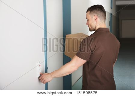 Close-up Of A Delivery Man Holding Cardboard Box Ringing The Door Bell