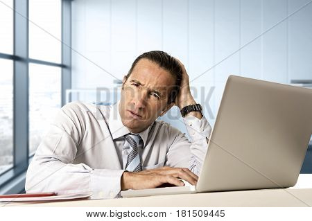 desperate senior businessman in crisis working on computer laptop at office desk in stress under pressure facing work problems at modern office in business district