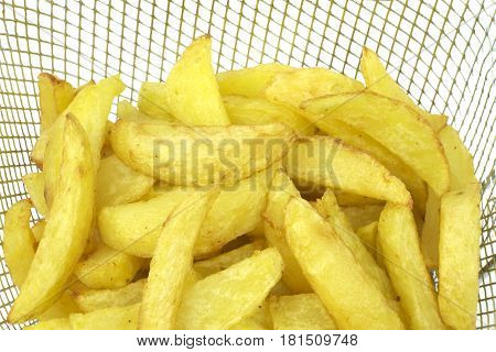 Fried potatoes in deep fryer close up image