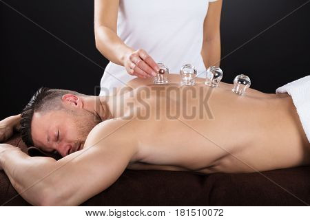 Female Therapist Placing Transparent Glass Cups On Man's Back In Spa