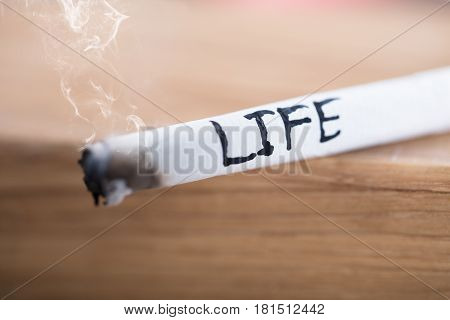 Burning Cigarette With Smoke And Written Word Life On Wooden Surface