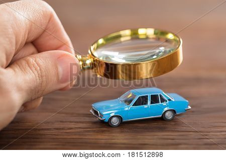 Close-up Of A Person Using Magnifying Glass On Car Model At Wooden Desk