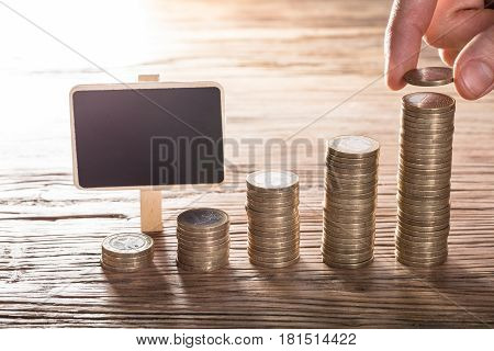 Person's Hand Placing A Coin Over The Stack With Blank Chalk Board On Wooden Table