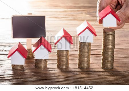 Person Hand Arranging House Models On Stacked Coins With Blank Chalk Board