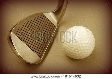 Golf club and golf ball isolated on brown background