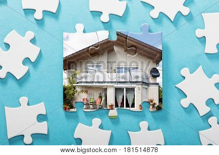 Close-up Of Incomplete House Puzzle On Blue Background