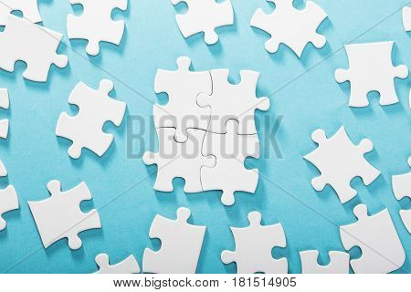 Elevated View Of White Jigsaw Puzzles On Blue Background