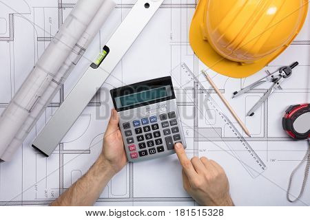 High Angle View Of Architect Hands Using Calculator Working On Blueprint