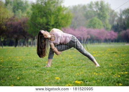 Young woman doing yoga in morning park. Parivtta baddha parsvakonasana, side angle pose.  Healthy lifestyle outdoor conception.