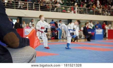 Martial art competitions - coach-judge with red flag looking at karate teenager's fighting, close up