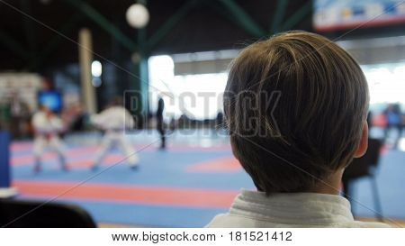 Karate competition - teenager boys looking at fighting on tatami arena, de-focused