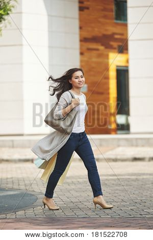 Ful--lenagth portrait of stylish attractive Vietnamese woman walking outdoors