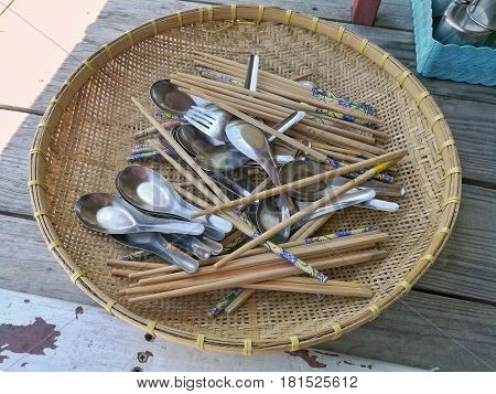 A group of spoon and bamboo chopstick in wicker basket. Spoon and bamboo chopstick after cleansing in Thai style food stall.