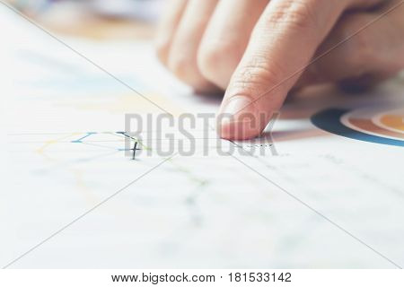 business woman hand working on wooden desk in office and there are many documents graphs. Can be attributed to financial articles.
