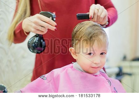 Haircut a little boy. The guy sits at the hairdresser. Wet hair on the head haircut and styling. A bottle with water and a comb in the hands of a girl.