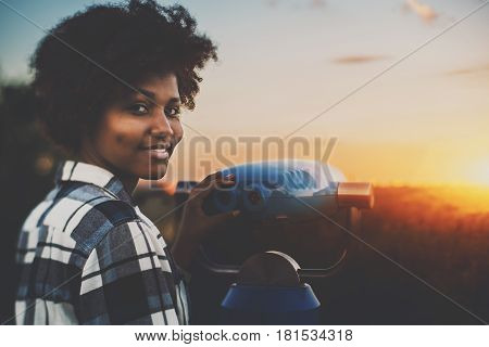 Cute biracial teenage female in plaid shirt is using street telescope to observe evening cityscape young black girl with curly hair and dimples near blue binocular is preparing to look at sunset