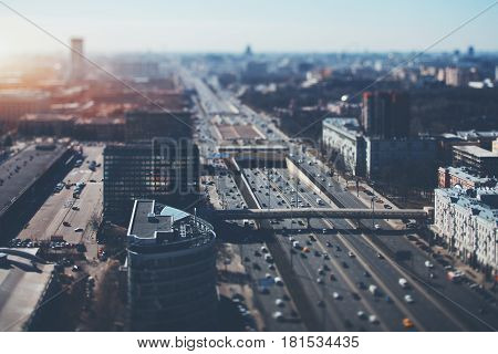 True tilt shift shooting of highway in metropolis from high point: multiple residential and office buildings parking many cars on busy streets of the city crosstown traffic sunny springtime