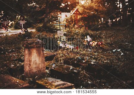 Old cracked mossy tombstone on graveyard with orthodox crosses above tombs in blurred background on moody autumn morning with copy space for your text message