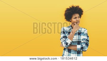 Thoughtful charming black teenage female in plaid shirt with curly afro hair on yellow background reflective young biracial girl looking aside with copy space for your advertising message