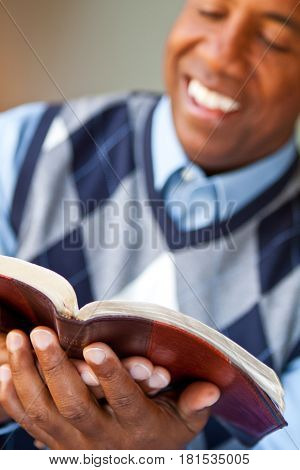 African American man reading the Bible at home.