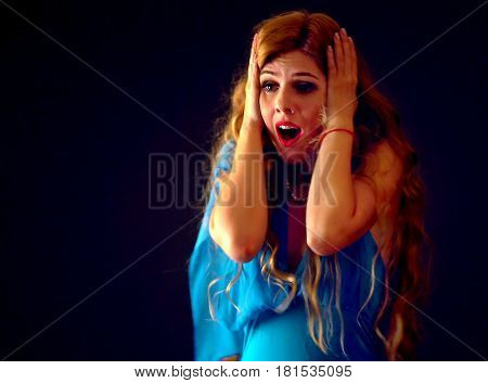 Frightened woman screaming with fear indoor at halloween night. Horror. Girl with tousled hair bawl black background. Attack of maniac.