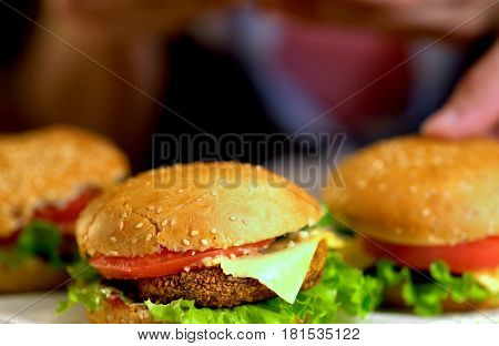 Hamburger fast food with ham on wooden board . Group of hamburger. Piece of cheese hanging from sandwich. Human hand holding cheeseburger is not in field. Easy sandwich recipes.
