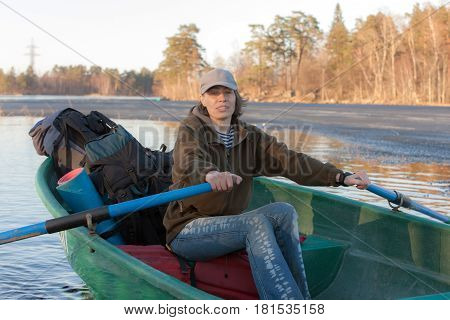 Woman with oars in boat on lake