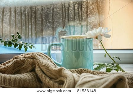 Composition with cup of hot tea on window sill