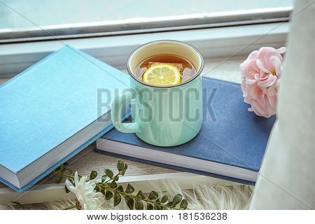 Cup of hot tea and books on window sill