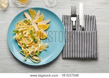 Plate of delicious pasta alfredo with chicken on served table
