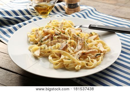 Plate with delicious Chicken Alfredo on wooden table