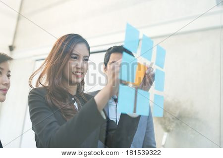 Business manager memo stick on the glass with her colleague