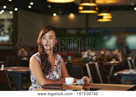 Beautiful Chinese woman enjoying cup of coffee in fancy restaurant