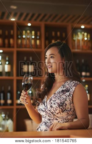 Young Asian woman tasting red wine in cellar