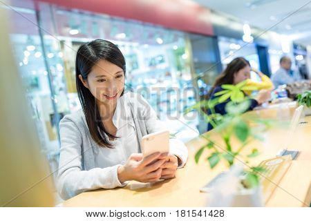 Woman looking in mobile phone in shopping mall
