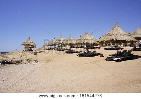 Straw umbrellas on the sandy beach on a Sunny day