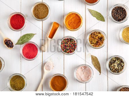Spices on white wooden background. Food flavor enhancers and